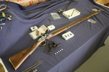A replica 18th century musket displayed alongside a variety of musket components in the archaeology collection. Artifacts from the collection aid researchers in interpreting new discoveries. Credit: Jonathan Fowler